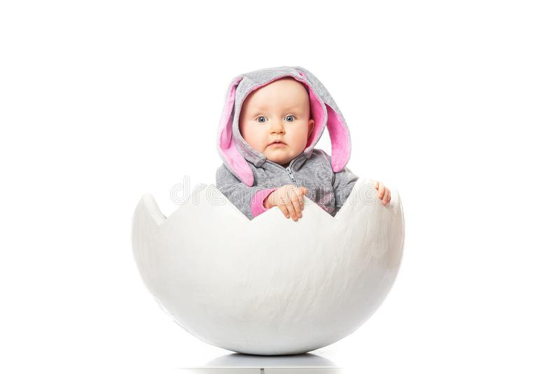 Μωρό σε ένα κοστούμι λαγουδάκι στο αυγό στο άσπρο υπόβαθρο καλύτερη έκπληξη Χαριτωμένος λίγο μωρό στο κοχύλι αυγών Κόμμα παιδιών  στοκ φωτογραφίες