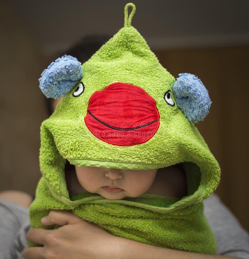 Μωρό σε ετοιμότητα στο mum μετά από το λουτρό σε μια αστεία πετσέτα στοκ φωτογραφία
