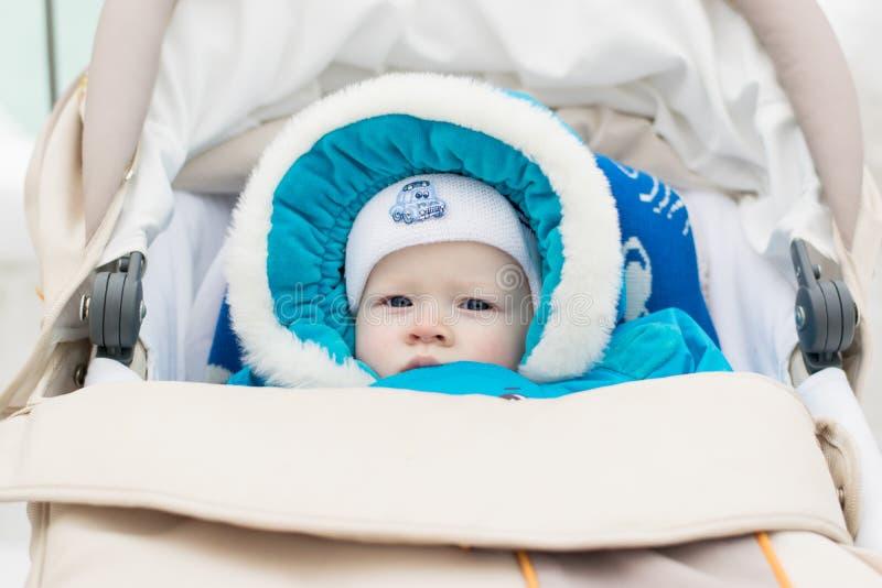 Μωρό σε μια μεταφορά μωρών καροτσακιών σε μια χειμερινή ημέρα στοκ φωτογραφία