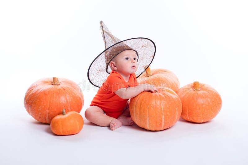 Μωρό στην πορτοκαλιά μπλούζα σε μια άσπρη συνεδρίαση υποβάθρου σε ένα witche στοκ εικόνες με δικαίωμα ελεύθερης χρήσης