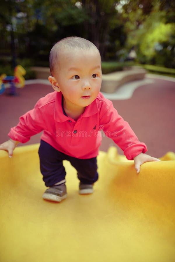 Μωρό στη φωτογραφική διαφάνεια παιδικών χαρών στοκ φωτογραφίες