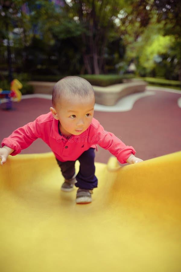 Μωρό στη φωτογραφική διαφάνεια παιδικών χαρών στοκ εικόνα με δικαίωμα ελεύθερης χρήσης