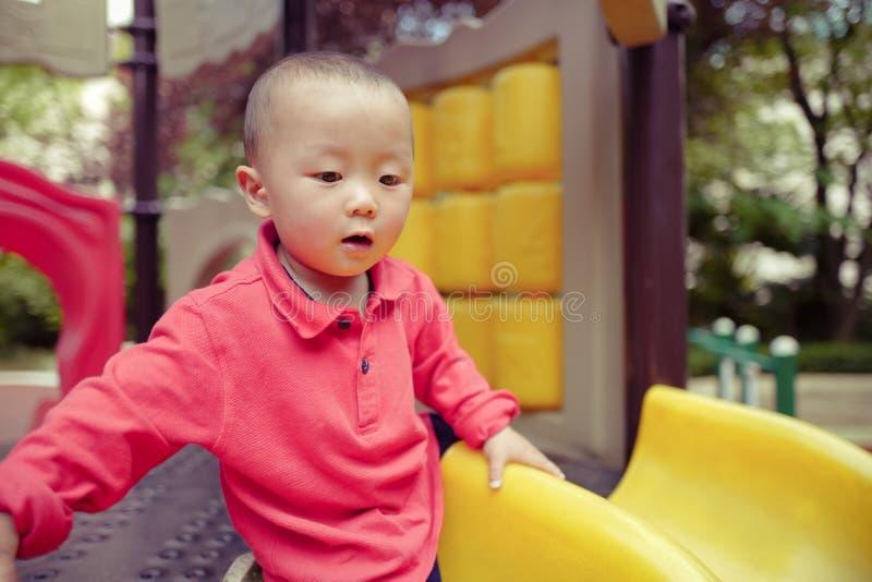 Μωρό στη φωτογραφική διαφάνεια παιδικών χαρών στοκ εικόνες