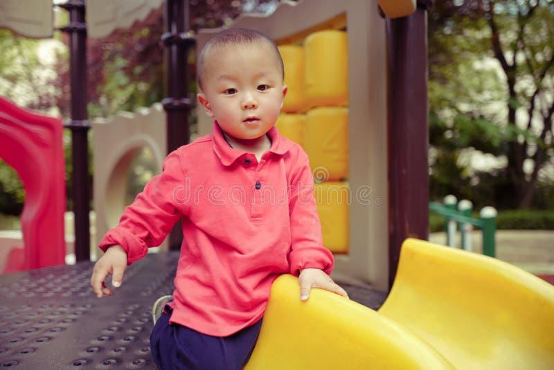 Μωρό στη φωτογραφική διαφάνεια παιδικών χαρών στοκ φωτογραφία με δικαίωμα ελεύθερης χρήσης