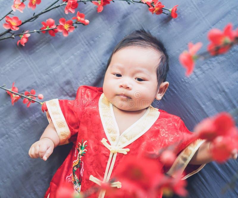 Μωρό στο κόκκινο φόρεμα στο μπλε ύφασμα με το λουλούδι και το κοίταγμα κινεζικό νέο έτος έννοιας στοκ εικόνα