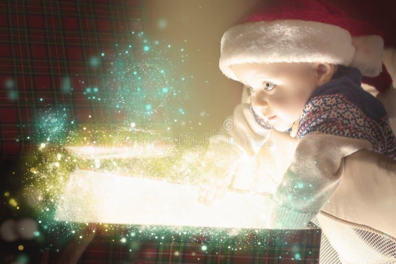 Μωρό Χριστουγέννων που ανοίγει ένα κιβώτιο παρόντος ή δώρων στοκ εικόνες