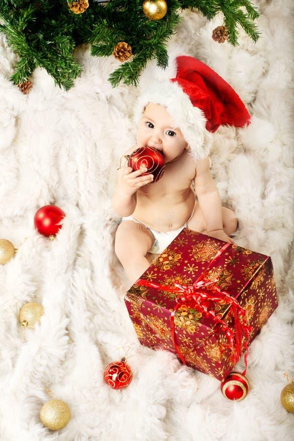 Μωρό Χριστουγέννων στο κόκκινο καπέλο στη γούνα και το eatin στοκ εικόνες