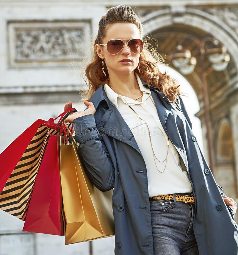 Μόδα-έμπορος με τις τσάντες αγορών που εξετάζει την απόσταση, Παρίσι στοκ εικόνες