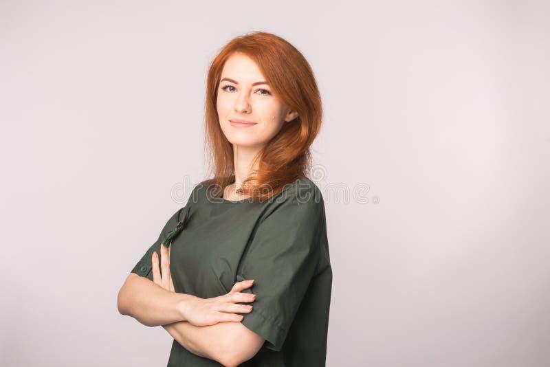 Μόδα και έννοια ανθρώπων - όμορφη νέα γυναίκα με την κόκκινη τρίχα που χαμογελά πέρα από το άσπρο υπόβαθρο με το διάστημα αντιγρά στοκ φωτογραφίες