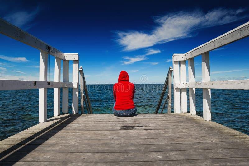 Μόνη γυναίκα στο κόκκινο πουκάμισο στην άκρη του λιμενοβραχίονα στοκ φωτογραφία με δικαίωμα ελεύθερης χρήσης