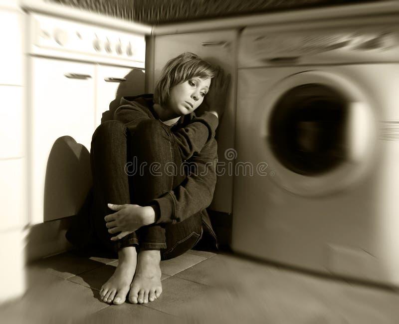 Μόνη και άρρωστη συνεδρίαση γυναικών στο πάτωμα κουζινών στην κατάθλιψη και τη θλίψη πίεσης στοκ εικόνα με δικαίωμα ελεύθερης χρήσης