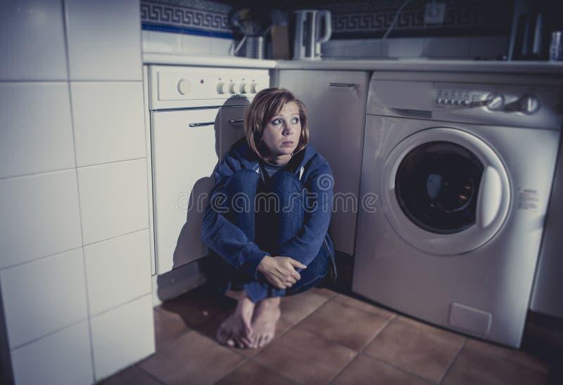 Μόνη και άρρωστη συνεδρίαση γυναικών στο πάτωμα κουζινών στην κατάθλιψη και τη θλίψη πίεσης στοκ εικόνες