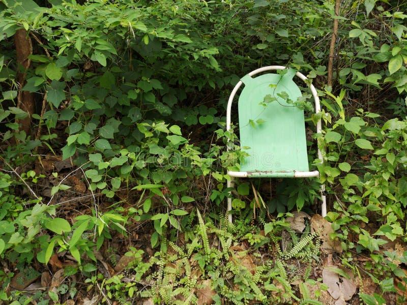 Μόνη και εγκαταλειμμένη μεταλλική πράσινη καρέκλα που χάνεται στη φύση στοκ φωτογραφίες με δικαίωμα ελεύθερης χρήσης