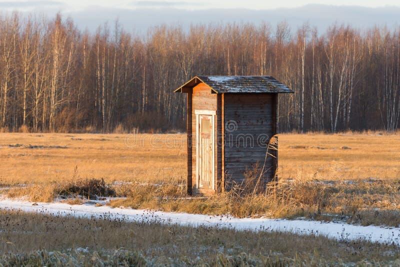 Μόνη μικρή σιταποθήκη τουαλετών οικοδόμησης σε έναν τομέα ενάντια στο σκηνικό του δάσους το χειμώνα στοκ εικόνες