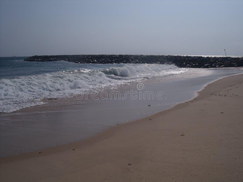 Μόνη παραλία με το ρέοντας νερό που καθοδηγείται από τις άσπρες πέτρες στοκ φωτογραφία