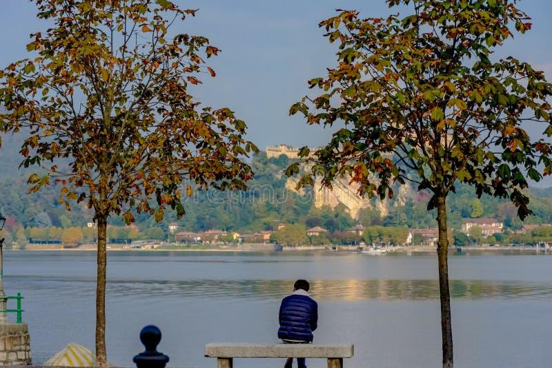 Μόνη συνεδρίαση ατόμων μεταξύ δύο δέντρων σε έναν πάγκο και της εξέτασης τη λίμνη Στην απόσταση μπορείτε να δείτε το νησί στο οπο στοκ εικόνα με δικαίωμα ελεύθερης χρήσης