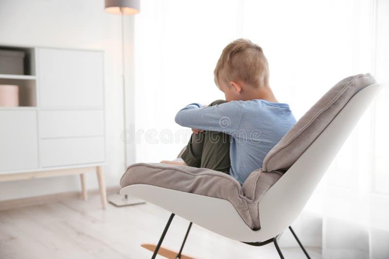 Μόνη συνεδρίαση μικρών παιδιών στην καρέκλα στο σπίτι στοκ εικόνα με δικαίωμα ελεύθερης χρήσης