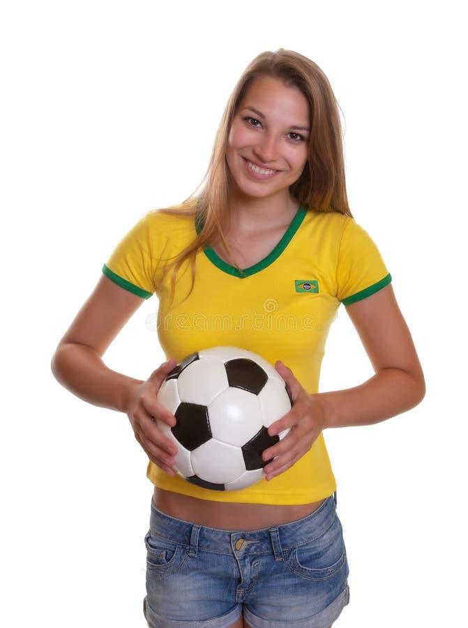 Μόνιμη γυναίκα στο βραζιλιάνο πουκάμισο με το ποδόσφαιρο στοκ φωτογραφίες με δικαίωμα ελεύθερης χρήσης