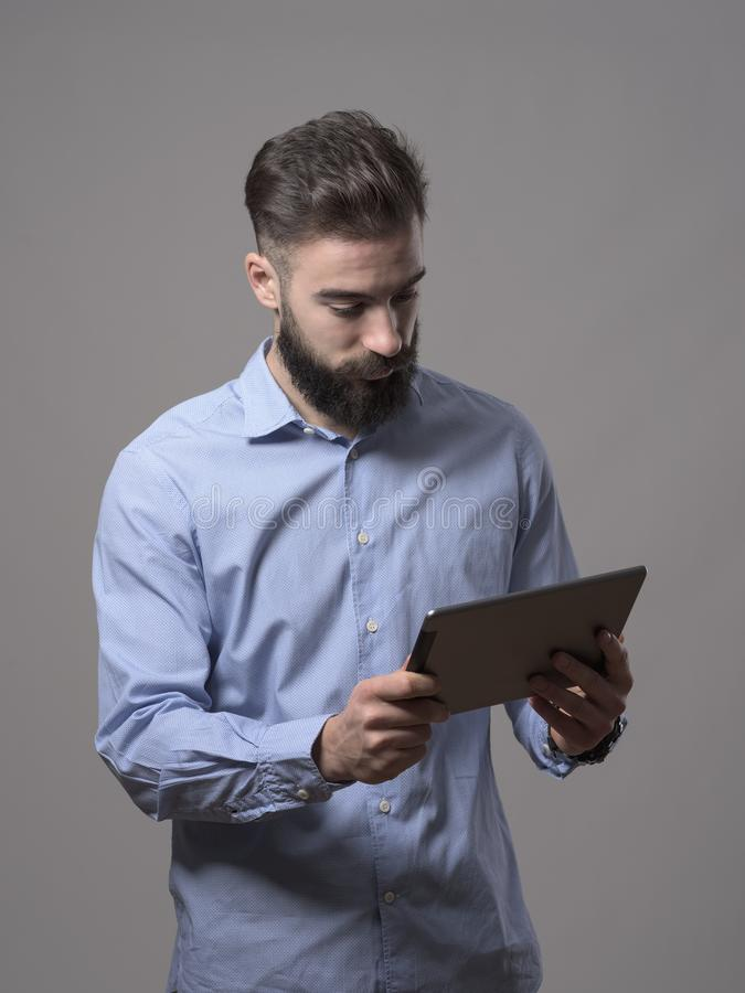Μόνιμη νέα ενήλικη γενειοφόρος εκμετάλλευση επιχειρησιακών ατόμων και προσοχή στον υπολογιστή ταμπλετών στοκ εικόνες με δικαίωμα ελεύθερης χρήσης