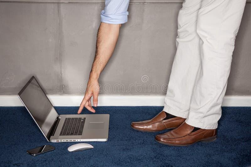 Μόνιμη προσπάθεια ατόμων να φθάσουν στο lap-top στην αρχή στοκ εικόνα με δικαίωμα ελεύθερης χρήσης