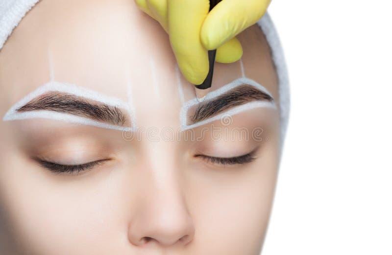 Μόνιμος αποζημιώστε τα φρύδια της όμορφης γυναίκας με τα παχιά brows στο σαλόνι ομορφιάς στοκ εικόνα