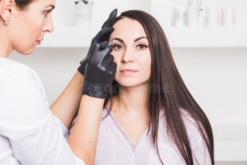 Μόνιμο makeup για τα φρύδια της όμορφης νέας γυναίκας στο σαλόνι ομορφιάς στοκ φωτογραφίες με δικαίωμα ελεύθερης χρήσης