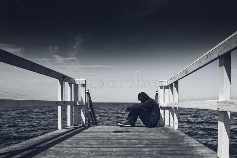 Μόνος νεαρός άνδρας στην άκρη της ξύλινης αποβάθρας στοκ εικόνες
