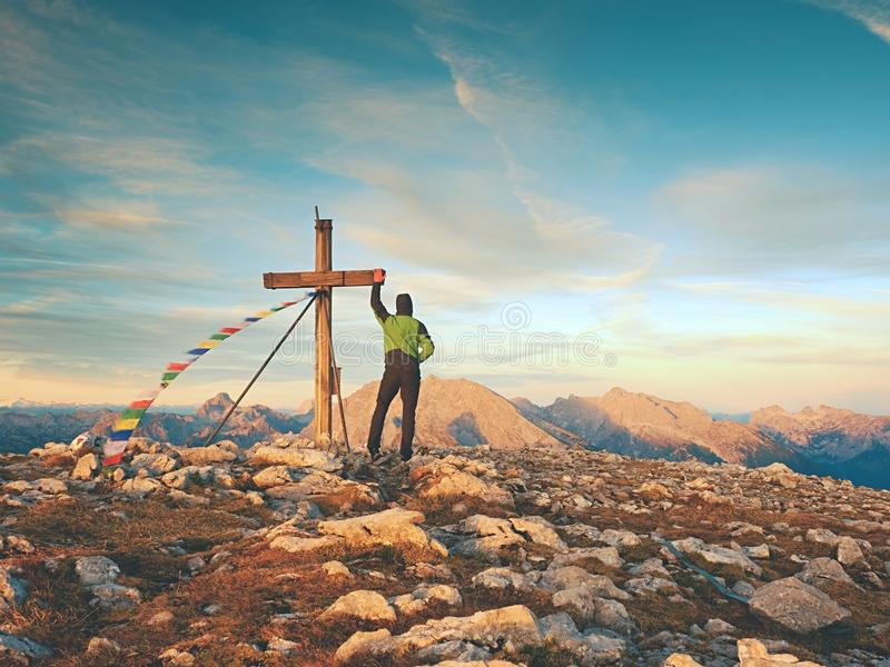 Μόνος ορειβάτης ατόμων κοντά στο σταυρό συνόδου κορυφής στην αιχμή, Άλπεις δολομίτη, Αυστρία Ηλιόλουστο θυελλώδες βράδυ στοκ εικόνα