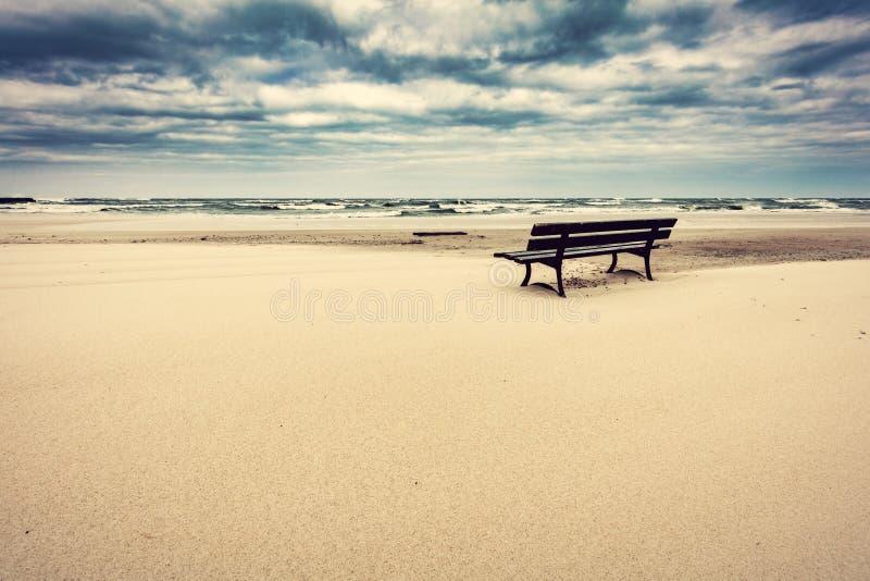 Μόνος πάγκος στην παραλία με την άποψη σχετικά με τη θάλασσα στοκ εικόνα