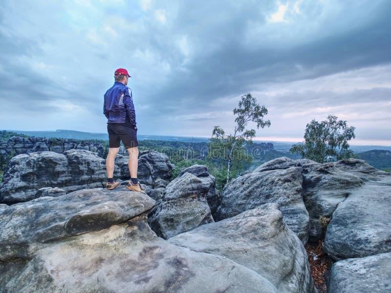 Μόνος τουρίστας με τη φίλαθλη στάση ενδυμάτων καπέλων του μπέιζμπολ στην άκρη απότομων βράχων στοκ φωτογραφίες με δικαίωμα ελεύθερης χρήσης