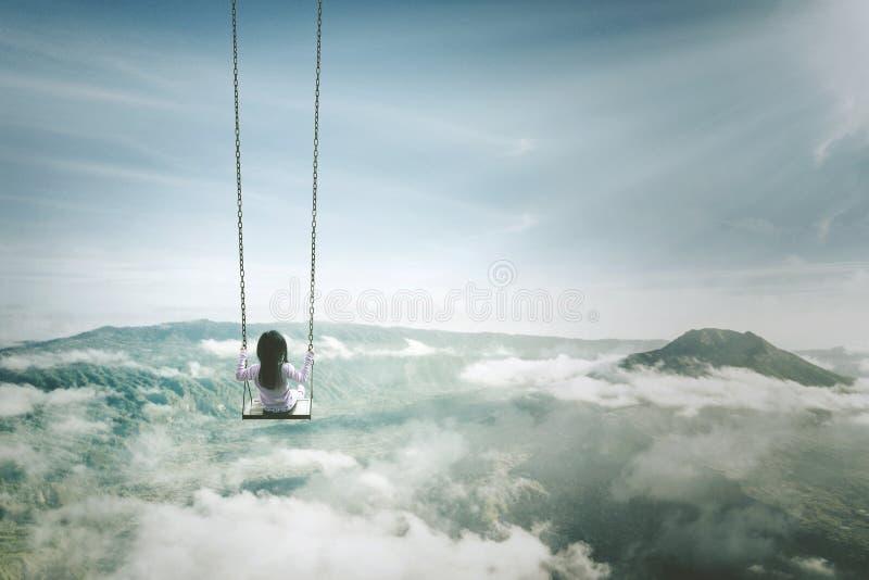 Μόνο κορίτσι με την ταλάντευση επάνω από το misty βουνό στοκ φωτογραφία
