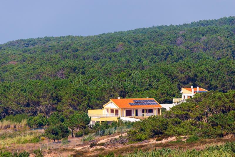Μόνο σπίτι με τον κήπο και ηλιακά πλαίσια στη στέγη στη φύση στοκ εικόνες