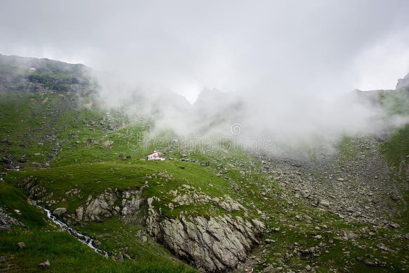 Μόνο σπίτι που απομονώνεται στο πράσινο όμορφο δύσκολο λιβάδι κοντά στα θαυμάσια χλοώδη βουνά που καλύπτονται στην ομίχλη στη Ρου στοκ φωτογραφίες με δικαίωμα ελεύθερης χρήσης