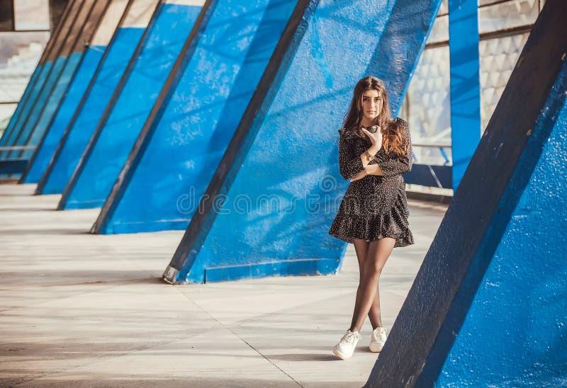 Μόνο όμορφο κορίτσι που στέκεται μεταξύ των μπλε στηλών της περιοχής πόλεων grunge Νέος καφές κατανάλωσης γυναικών στο αστικό διά στοκ εικόνες με δικαίωμα ελεύθερης χρήσης