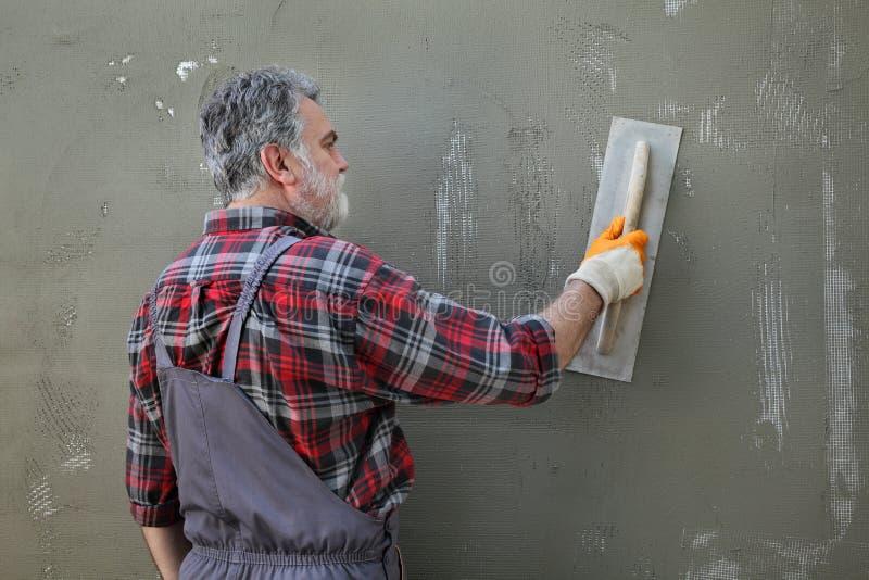 Μόνωση τοίχων, κονίαμα διάδοσης πέρα από το πλέγμα και styrofoam, κάλυψη πολυστυρολίου στοκ εικόνα με δικαίωμα ελεύθερης χρήσης