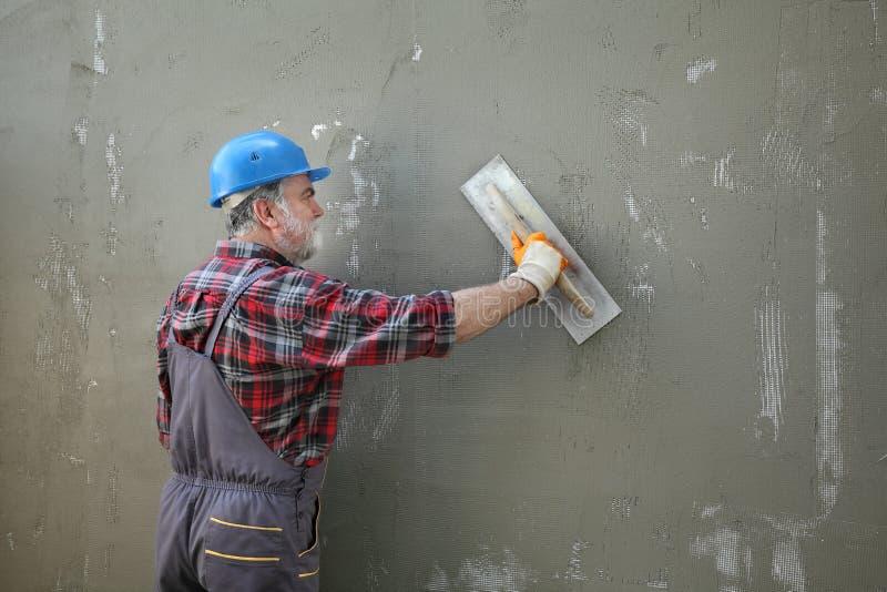 Μόνωση τοίχων, κονίαμα διάδοσης πέρα από το πλέγμα και styrofoam, κάλυψη πολυστυρολίου στοκ φωτογραφία