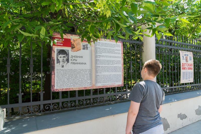 Μόσχα, Ρωσία - 2 Ιουνίου 2016 Αγόρι εφήβων που διαβάζει ένα τεμάχιο του βιβλίου των παιδιών του πολέμου στην οδό Myasnitskaya στοκ φωτογραφία με δικαίωμα ελεύθερης χρήσης