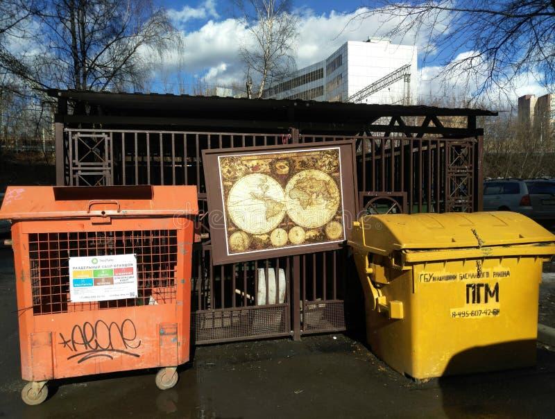 Μόσχα, RF 26 Μαρτίου 2019: ο αρχαίος χάρτης εικόνα-γρίφων του κόσμου κρεμά στην πόλη dumpster μεταξύ των απορριμάτων δύο στοκ φωτογραφίες με δικαίωμα ελεύθερης χρήσης