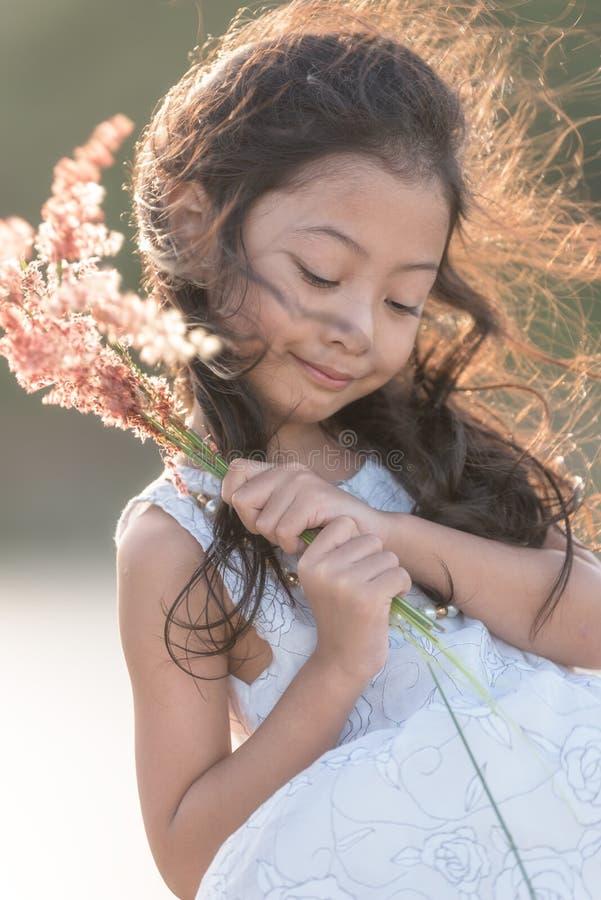 μόδα παιδιών Χαριτωμένος λίγο ασιατικό κορίτσι που φορά τα άσπρες ενδύματα και τη χλόη λουλουδιών στο χέρι της στοκ φωτογραφία με δικαίωμα ελεύθερης χρήσης