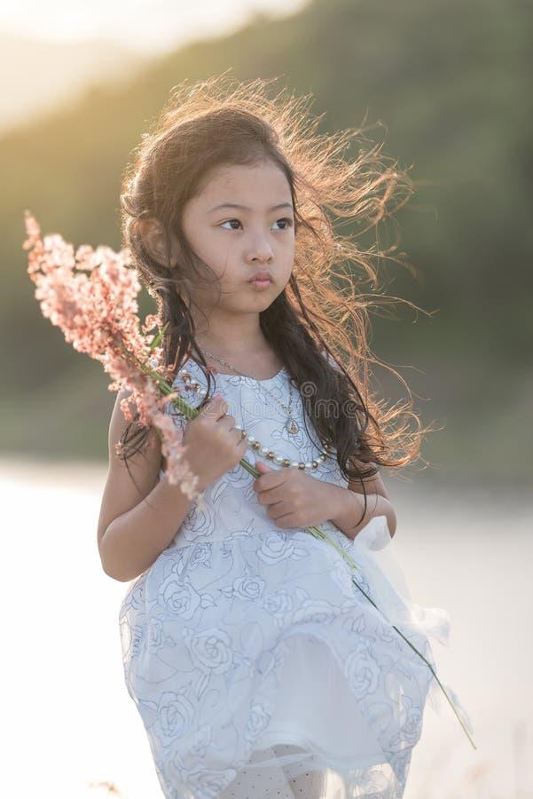 μόδα παιδιών Χαριτωμένος λίγο ασιατικό κορίτσι που φορά τα άσπρες ενδύματα και τη χλόη λουλουδιών στο χέρι της στοκ εικόνες