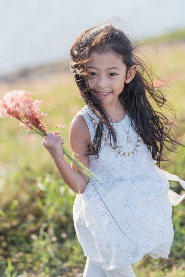 μόδα παιδιών Χαριτωμένος λίγο ασιατικό κορίτσι που φορά τα άσπρες ενδύματα και τη χλόη λουλουδιών στο χέρι της στοκ εικόνα με δικαίωμα ελεύθερης χρήσης