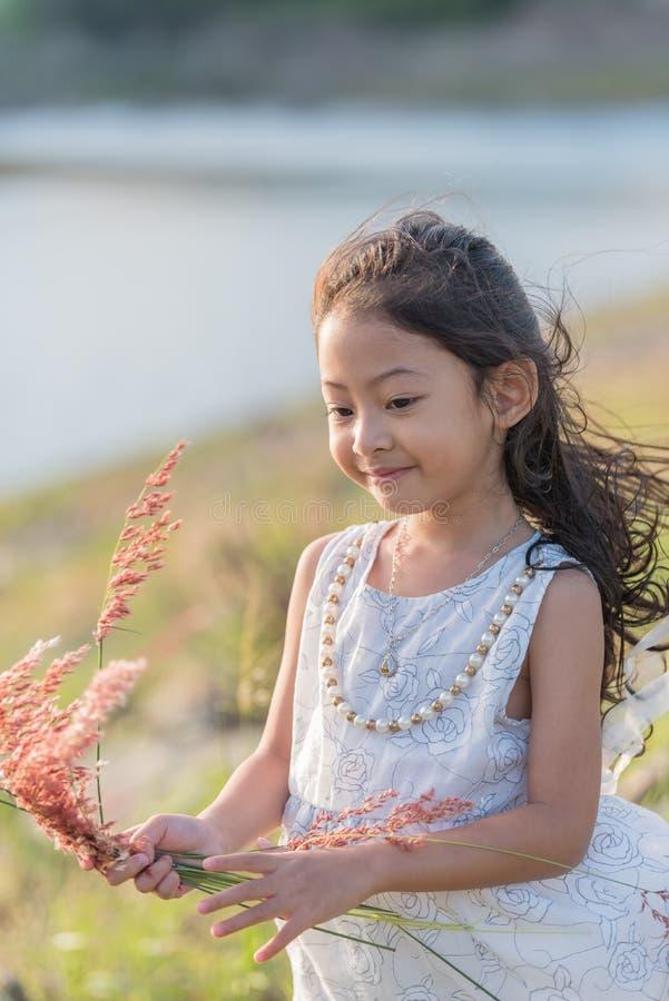 μόδα παιδιών Χαριτωμένος λίγο ασιατικό κορίτσι που φορά τα άσπρες ενδύματα και τη χλόη λουλουδιών στο χέρι της στοκ εικόνες με δικαίωμα ελεύθερης χρήσης
