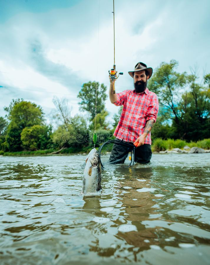 Μύγα που αλιεύει για την πέστροφα Αλιεία στον ποταμό Πιάνει ένα ψάρι Σύλληψη ενός μεγάλου ψαριού με έναν πόλο αλιείας Μύγα που αλ στοκ φωτογραφία