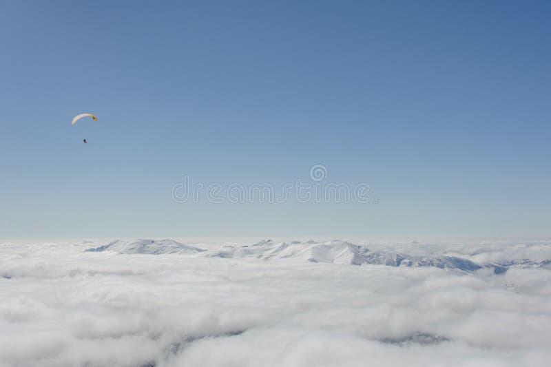 Μύγα Snowboarders σε ένα ανεμόπτερο επάνω από τα σύννεφα στοκ εικόνα με δικαίωμα ελεύθερης χρήσης