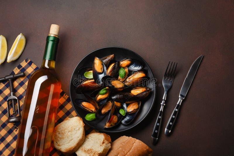 Μύδια θαλασσινών και φύλλα βασιλικού σε ένα μαύρο πιάτο με το μπουκάλι κρασιού, το ανοιχτήρι, τη φέτα ψωμιού, το δίκρανο και το μ στοκ φωτογραφία