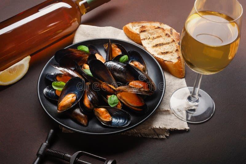 Μύδια θαλασσινών και φύλλα βασιλικού σε ένα μαύρο πιάτο με το μπουκάλι κρασιού, wineglass, ανοιχτήρι, φέτες ψωμιού, burlap στο σκ στοκ φωτογραφίες με δικαίωμα ελεύθερης χρήσης