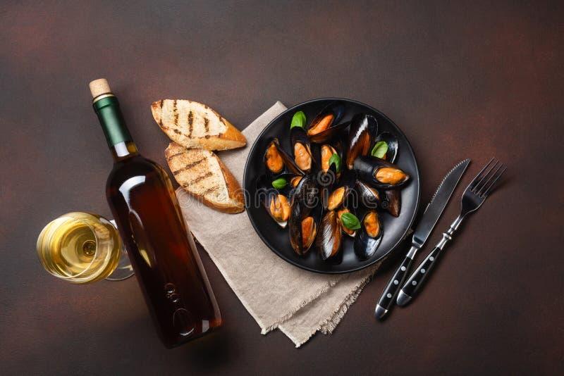 Μύδια θαλασσινών και φύλλα βασιλικού σε ένα μαύρο πιάτο με το μπουκάλι κρασιού, wineglass, φέτες ψωμιού, δίκρανο, μαχαίρι, burlap στοκ εικόνα