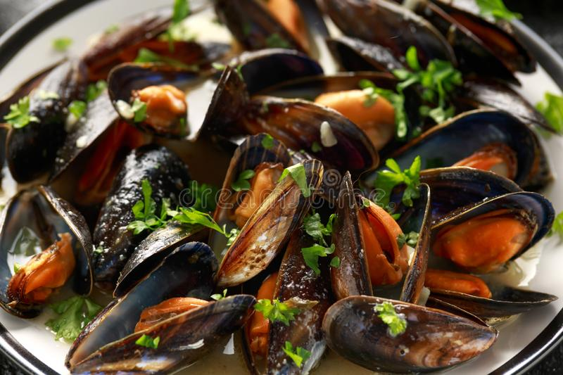 Μύδια με το άσπρα κρασί, το σκόρδο, το λεμόνι και τα χορτάρια σε ένα πιάτο, τηγανιτές πατάτες rustick υπόβαθρο Θαλασσινά στοκ εικόνα με δικαίωμα ελεύθερης χρήσης