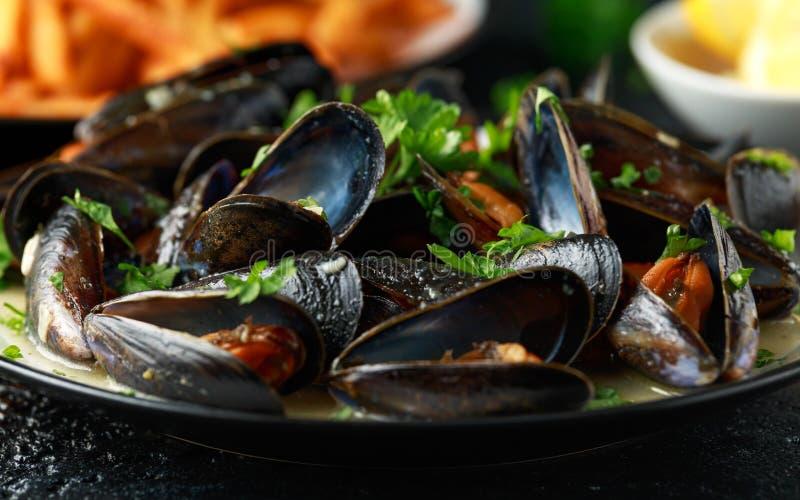Μύδια με το άσπρα κρασί, το σκόρδο, το λεμόνι και τα χορτάρια σε ένα πιάτο, τηγανιτές πατάτες rustick υπόβαθρο Θαλασσινά στοκ εικόνες με δικαίωμα ελεύθερης χρήσης