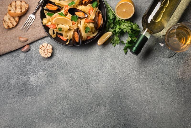 Μύδια, φρυγανιές ψωμιού και άσπρο κρασί στον πίνακα πετρών Τοπ άποψη με το διάστημα αντιγράφων στοκ εικόνα